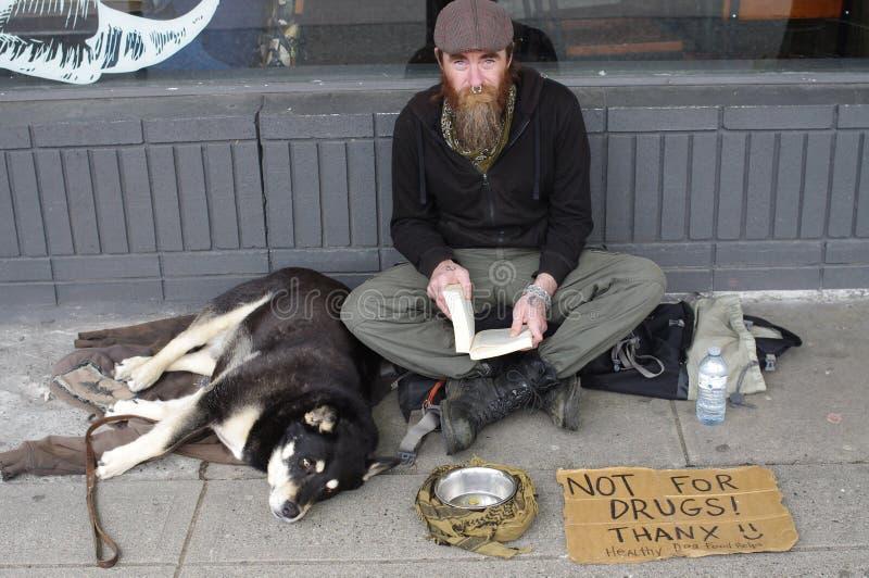 Homem desabrigado com um animal de estimação que guarda o livro foto de stock royalty free