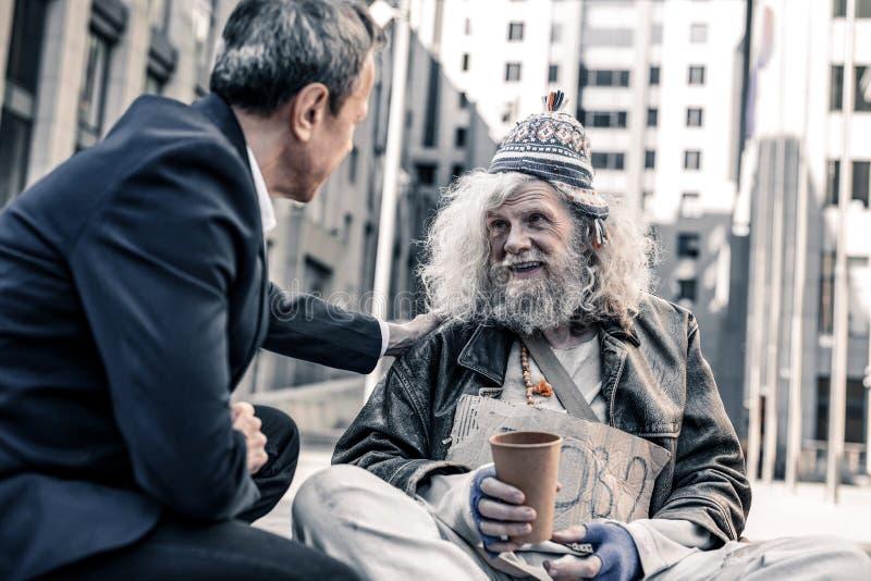 Homem desabrigado de cabelos compridos feliz de sorriso que toma o dinheiro do homem de negócios amável imagens de stock