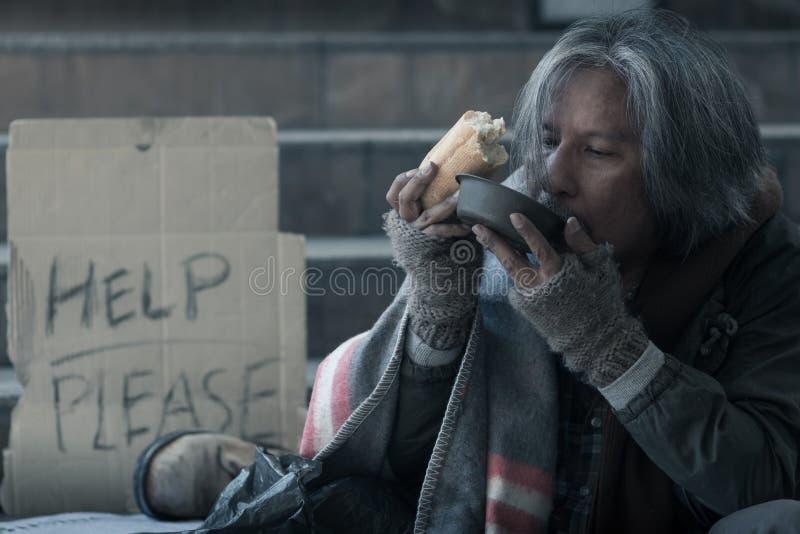 Homem desabrigado na escada da rua da passagem na cidade que come povos da bondade do formulário do pão e do leite para dá-lo imagem de stock