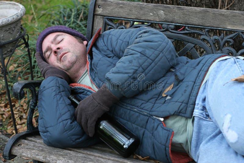 Homem desabrigado - no banco de parque imagem de stock