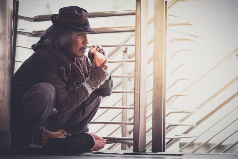 Homem desabrigado no canto da rua da passagem na cidade que come povos da bondade do formulário do pão para dá-lo foto de stock royalty free
