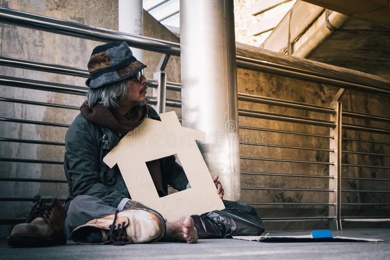 Homem desabrigado no canto da rua da passagem nos povos de espera da bondade da cidade para dar o dinheiro ou o alimento fotos de stock royalty free