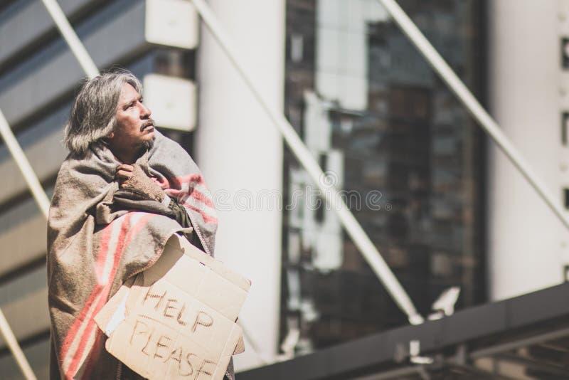 Homem desabrigado que acorda na rua da passagem nos povos de espera da bondade da cidade para dar o dinheiro ou o alimento foto de stock
