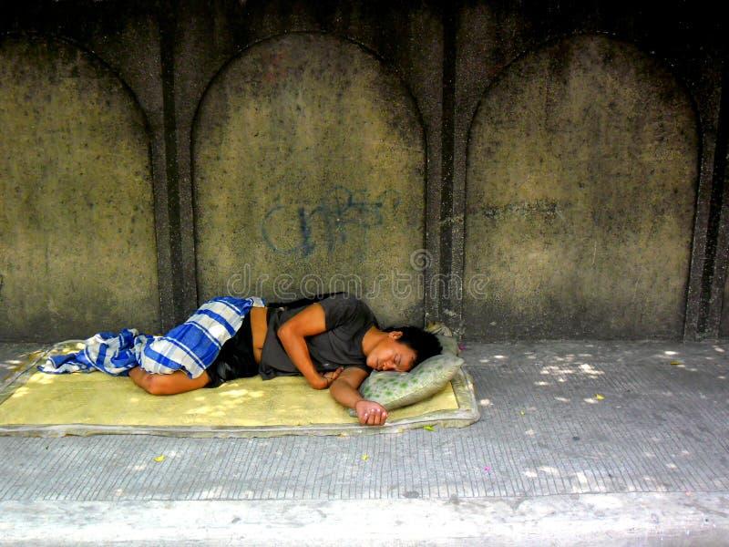 Homem desabrigado que dorme em um passeio imagens de stock