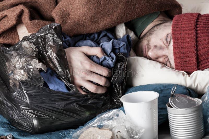 Homem desabrigado que dorme na rua imagens de stock