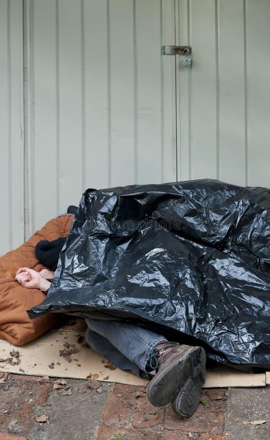 Homem desabrigado que dorme sob o encerado plástico foto de stock royalty free