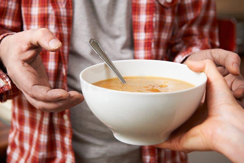 Homem desabrigado que está sendo entregado a bacia de sopa pelo voluntário fotografia de stock