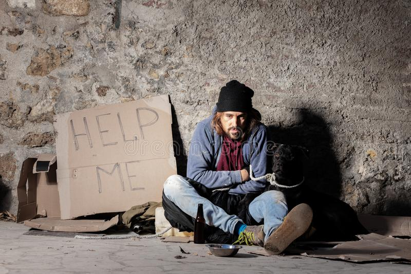 Homem desabrigado que senta-se na rua com um cão fotografia de stock