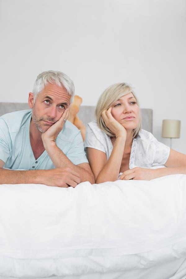 Homem desagradado e mulher maduros que encontram-se na cama fotos de stock