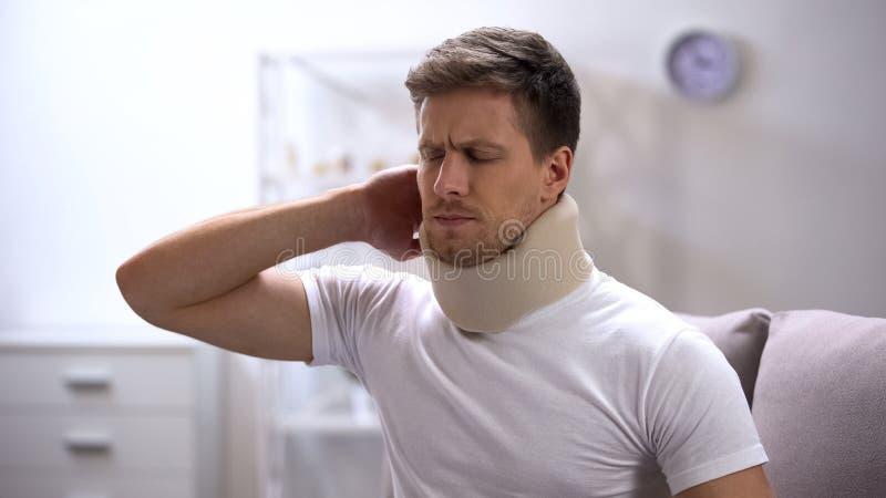 Homem desagradado no colar cervical da espuma que sente de repente a dor no pescoço, traumatismo fotografia de stock royalty free