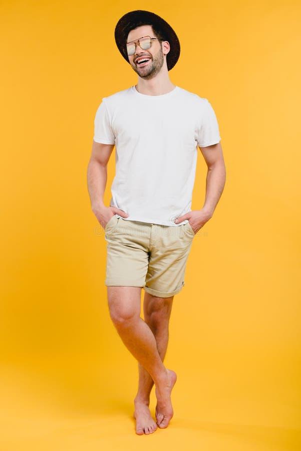 homem descalço dos jovens no short e nos óculos de sol que estão com mãos em uns bolsos e no riso imagens de stock