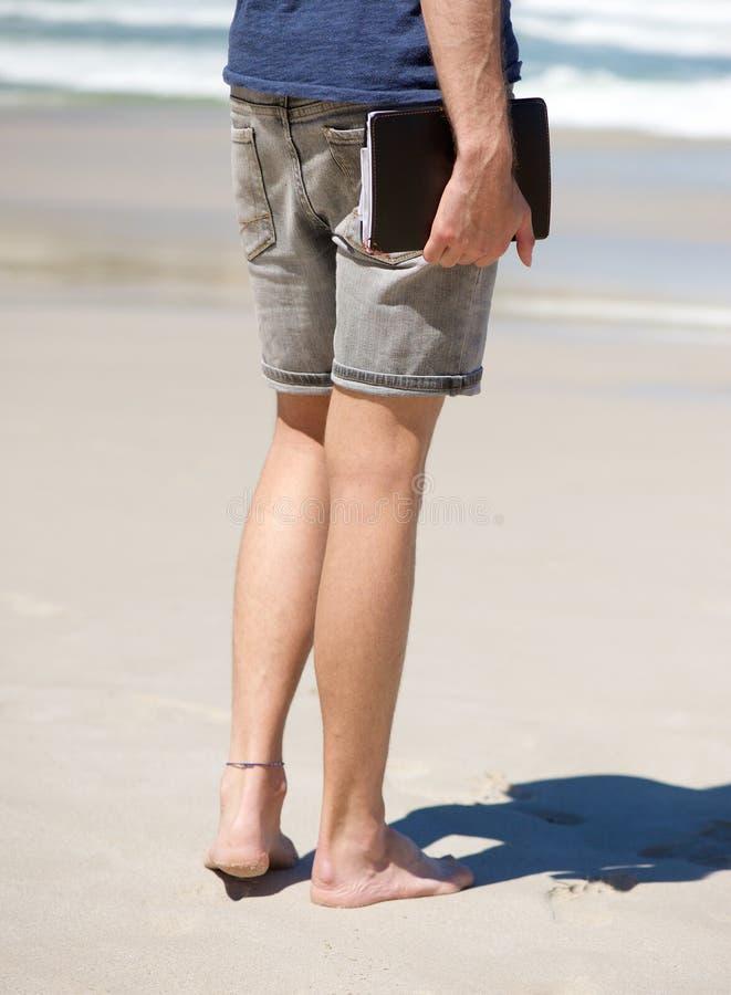 Homem descalço que guarda o livro da agenda na praia fotos de stock