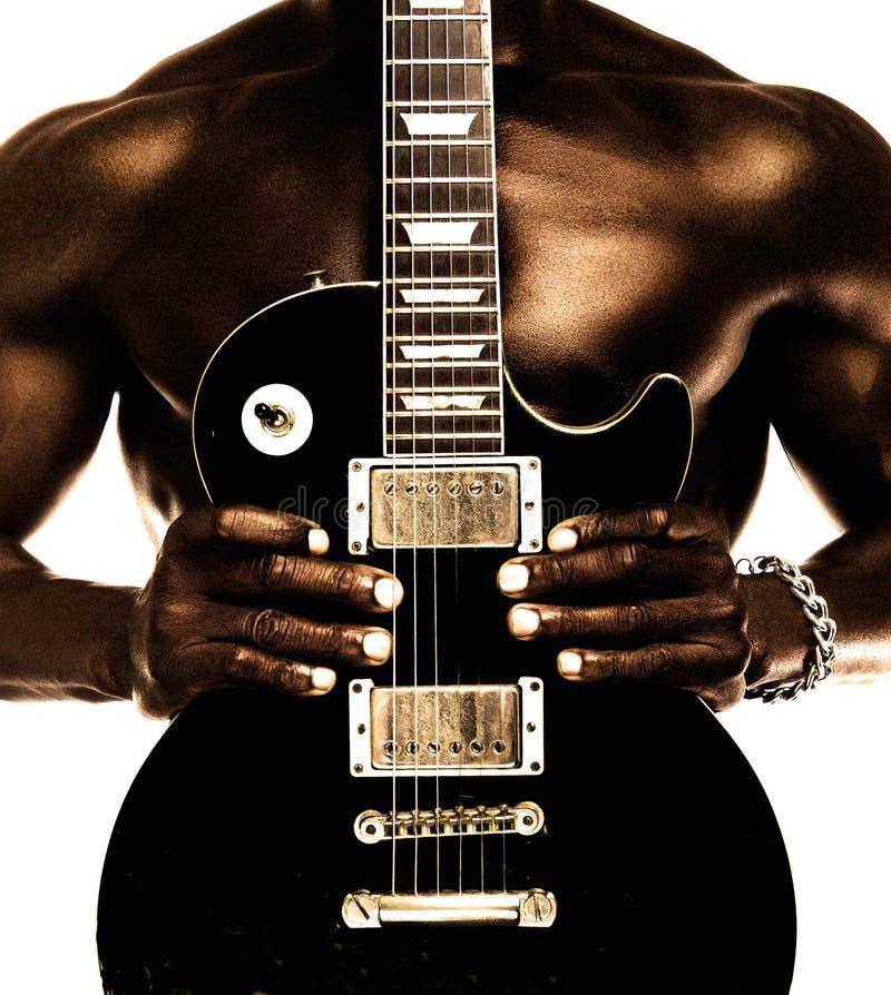 Homem descamisado afro-americano que guarda a guitarra elétrica imagem de stock royalty free