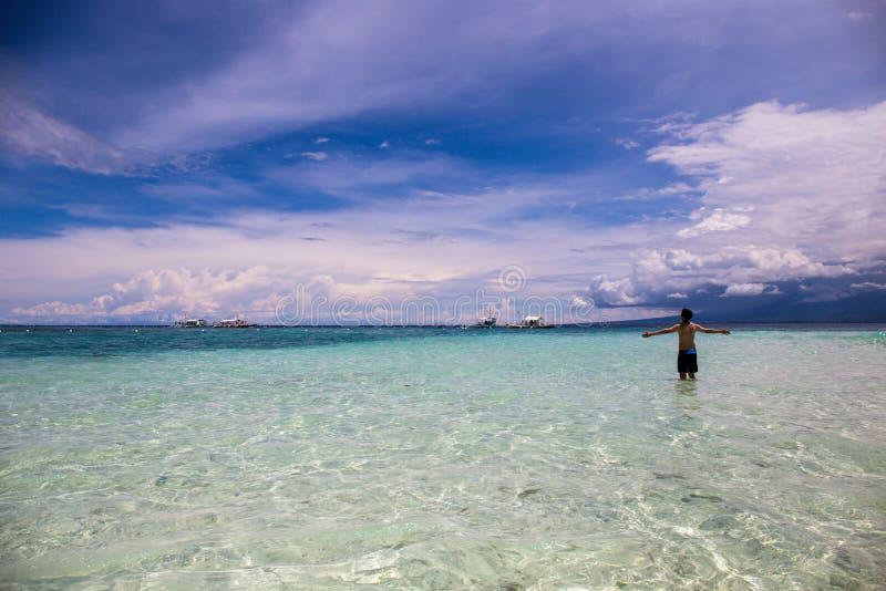 Homem descamisado feliz e alegre no roupa de banho que levanta as mãos acima na água da praia imagem de stock royalty free