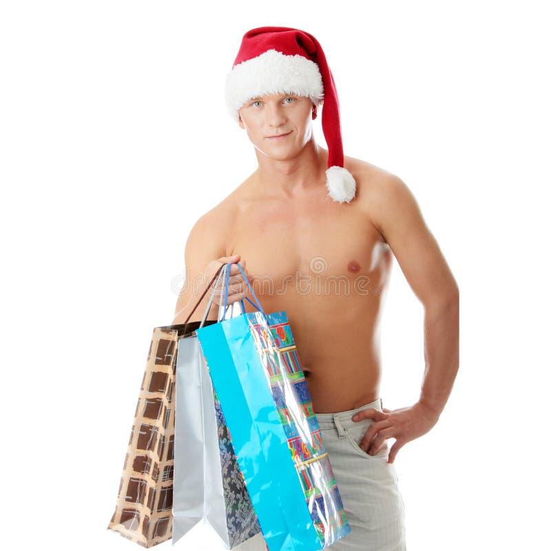 Homem descamisado muscular 'sexy' no chapéu de Papai Noel imagens de stock royalty free