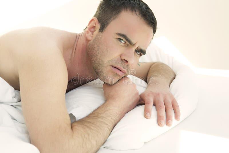 Homem descamisado na cama que olha a câmera imagem de stock royalty free
