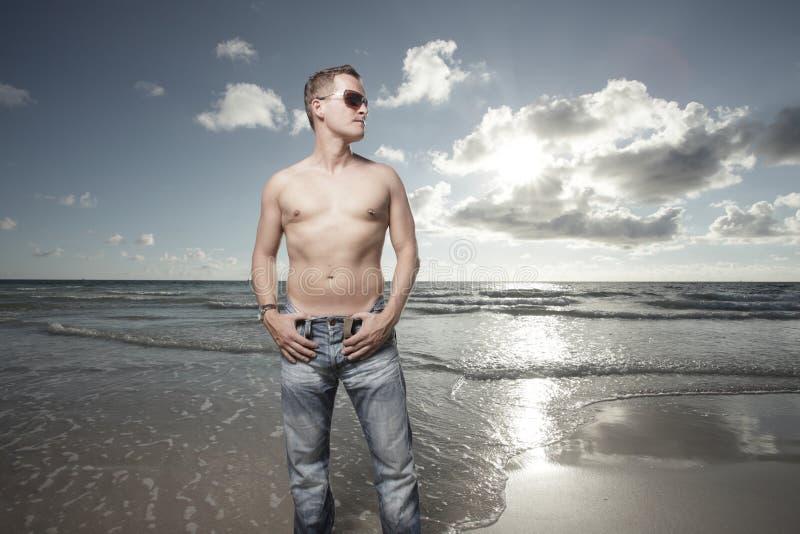 Homem descamisado na praia foto de stock
