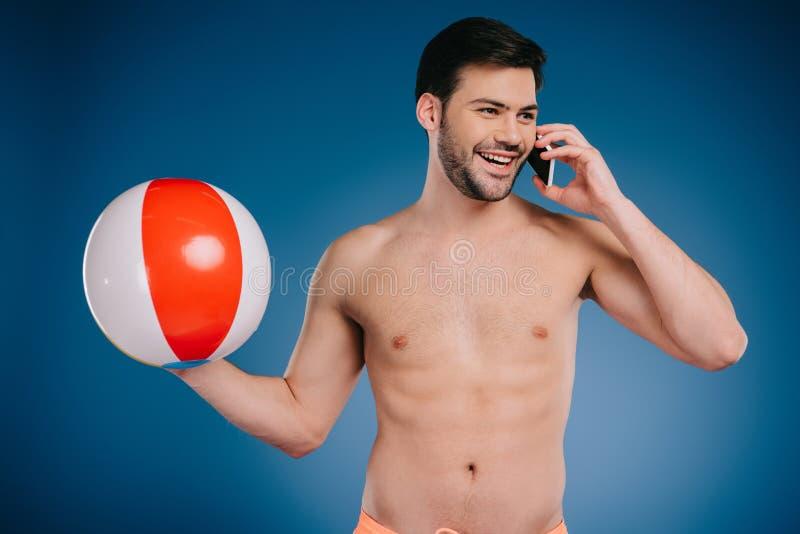 homem descamisado novo de sorriso que guarda a bola de praia e que fala pelo smartphone fotos de stock royalty free