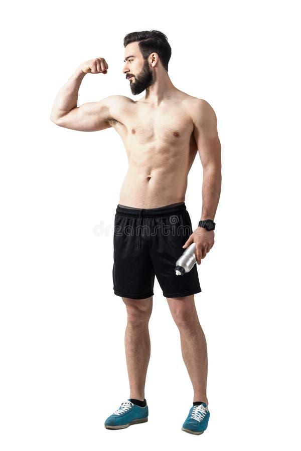 Homem descamisado novo do ajuste forte que dobra o músculo do bíceps e que guarda a garrafa de água imagens de stock royalty free