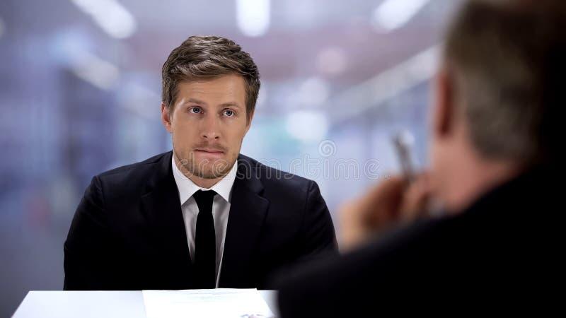 Homem desconfiado apresentando curriculum vitae para gerente da empresa, entrevista de emprego fotografia de stock royalty free