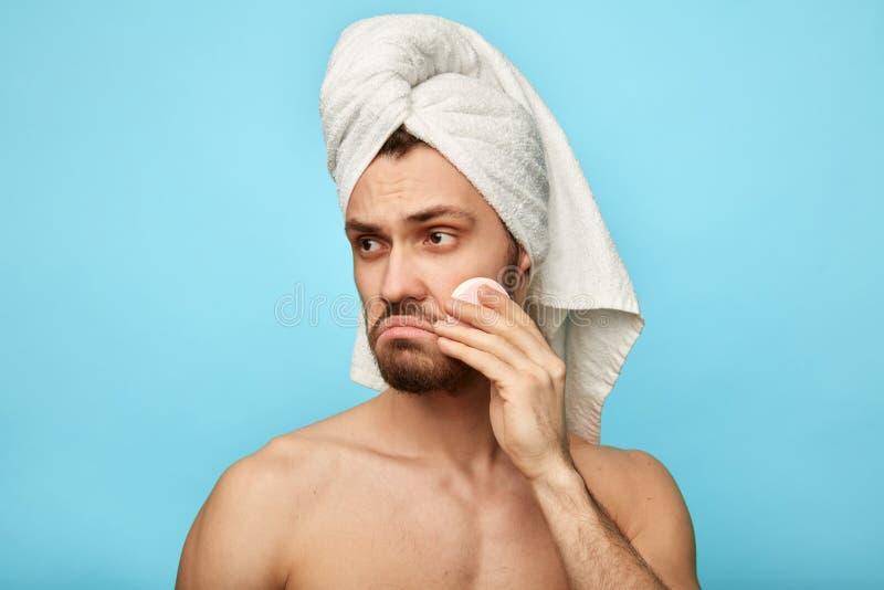 Homem descontentado infeliz triste que limpa seu mordente e que olha de lado fotos de stock