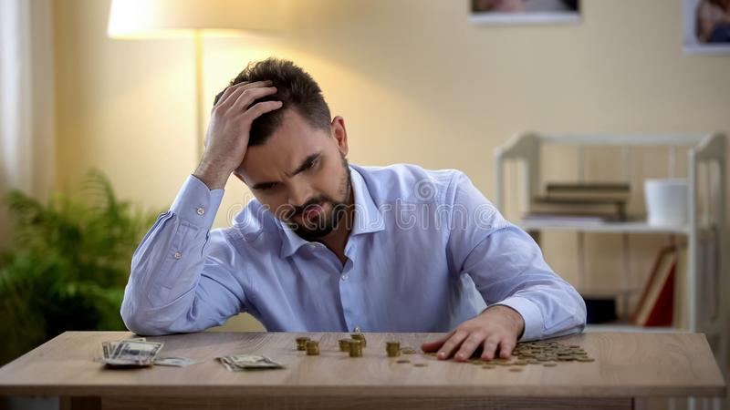 Homem desempregado novo irritado que senta-se na tabela, contando economias, crise financeira foto de stock royalty free