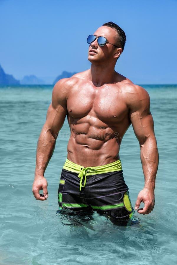Homem despido molhado novo atlético que levanta no oceano no short da placa fotos de stock royalty free