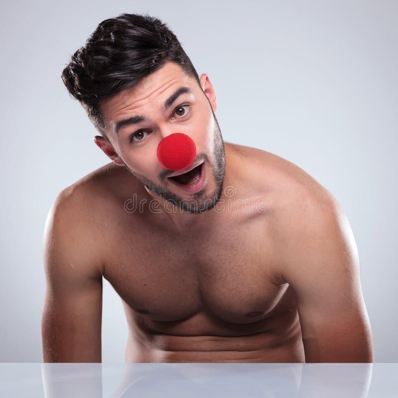 Homem despido novo surpreendido com o nariz vermelho do palhaço foto de stock
