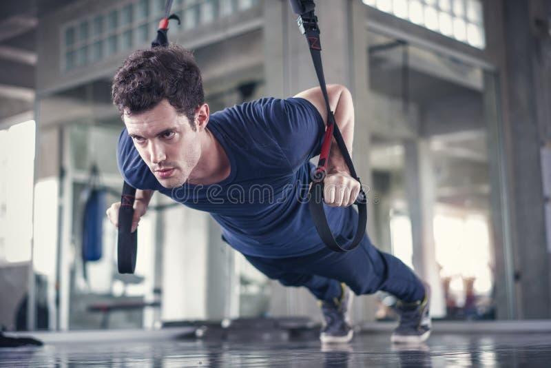 Homem desportivo do atleta que faz o exercício com as correias do trx da aptidão para reforçar seu músculo abdominal no gym foto de stock