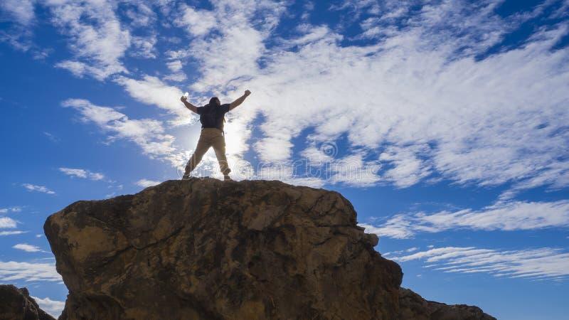 Homem desportivo feliz com a trouxa e os braços acima aumentados que estão e na rocha e que olham o litoral e as montanhas em fotos de stock