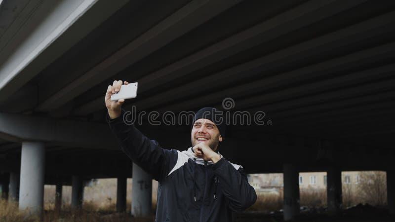 Homem desportivo feliz que toma o retrato do selfie com o smartphone após a formação no lugar urbano do ar livre no inverno fotografia de stock