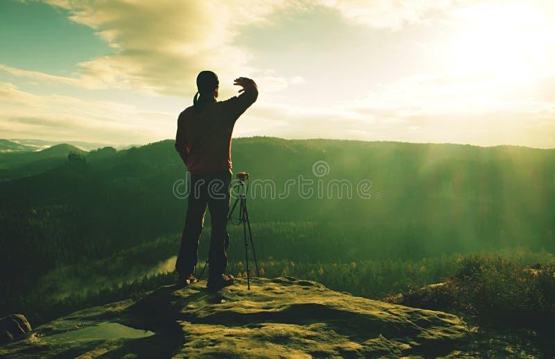 Homem desportivo no pico de montanha que olha no vale da montanha foto de stock