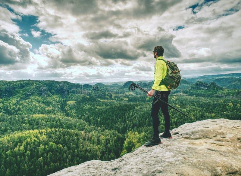 Homem desportivo no pico de montanha que olha no vale da montanha foto de stock royalty free