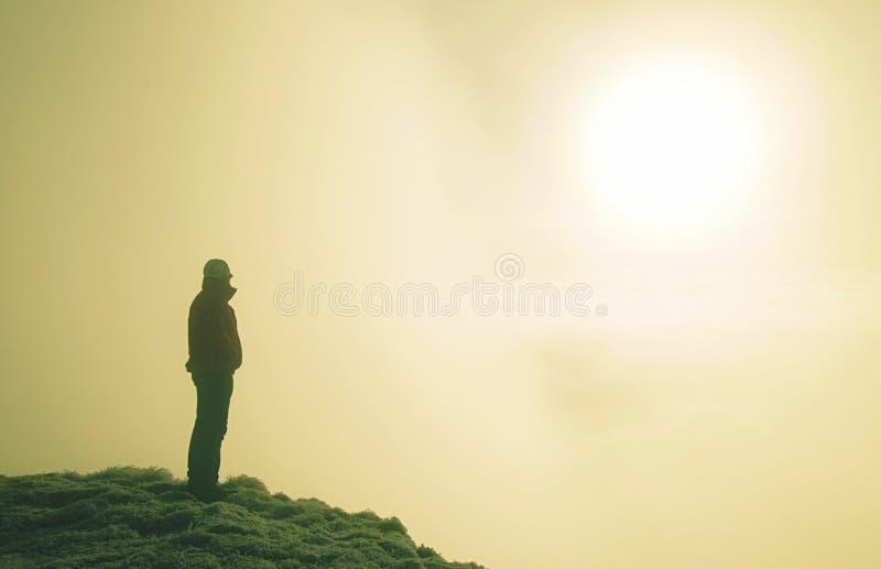 Homem desportivo no pico de montanha que olha no vale da montanha fotografia de stock