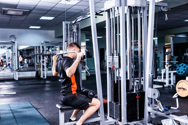 Homem desportivo no sportswear que faz o exercício com um peso pesado imagens de stock