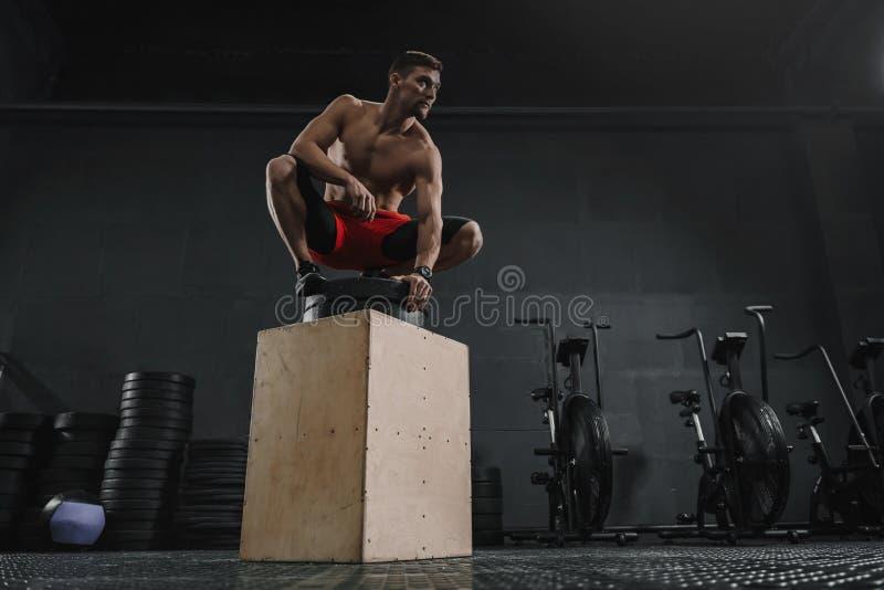 Homem desportivo novo que descansa após o exercício do salto da caixa no gym imagem de stock