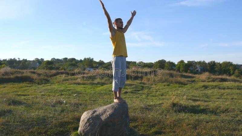 Homem desportivo novo que está na pedra na pose da ioga exterior A ioga praticando do iogue move-se e posiciona-se na natureza at imagem de stock royalty free