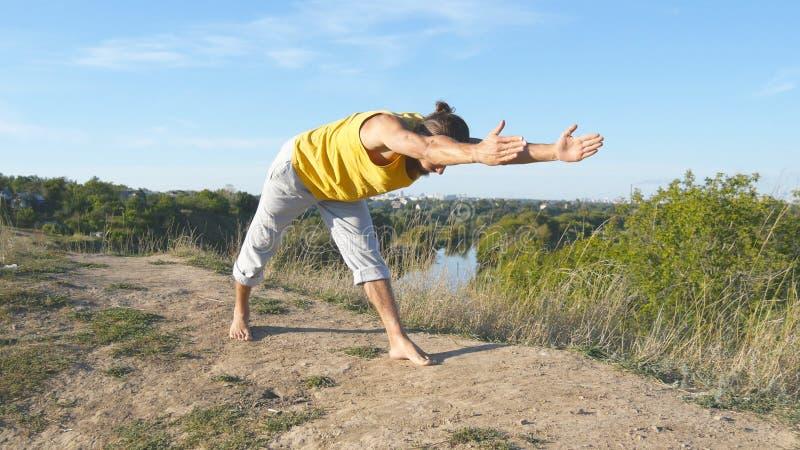 Homem desportivo novo que está na pose da ioga exterior A ioga praticando do indivíduo caucasiano move-se e posiciona-se na natur fotografia de stock royalty free