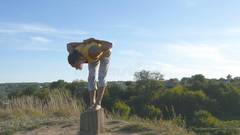 Homem desportivo novo que está na pose da ioga exterior A ioga praticando do indivíduo caucasiano move-se e posiciona-se na natur imagens de stock