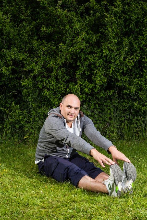 Homem desportivo que faz esticando o exercício no prado verde imagem de stock royalty free