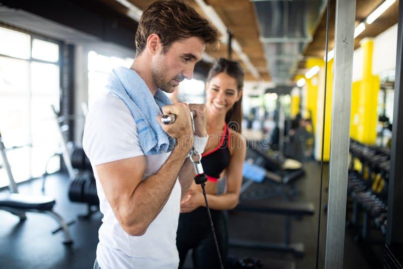Homem desportivo que faz exerc?cios do peso com aux?lio de seu instrutor pessoal fotografia de stock royalty free