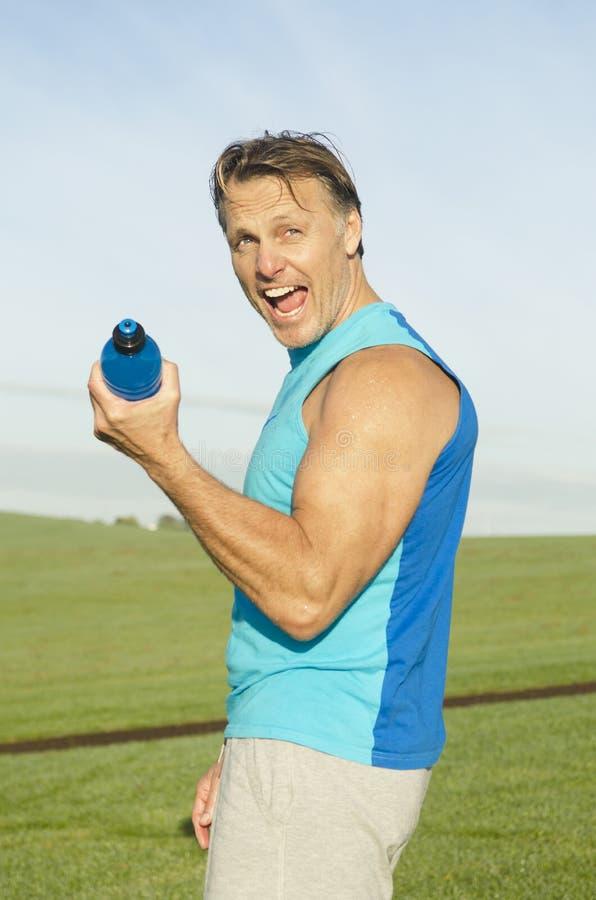 Homem desportivo que flexiona seus músculos imagens de stock