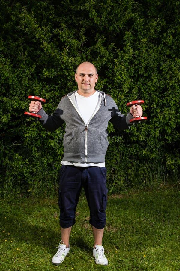 Homem desportivo que guarda dois pesos vermelhos no ar foto de stock royalty free