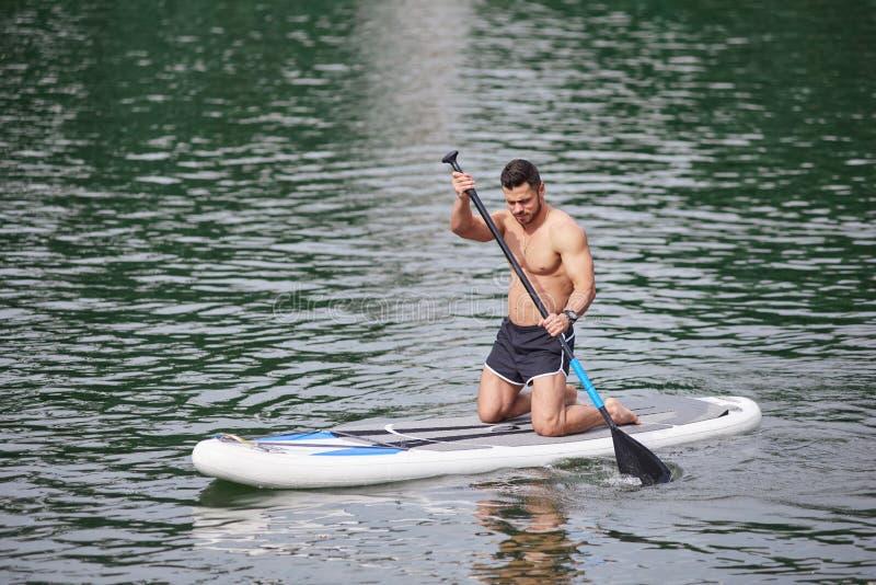 Homem desportivo que mantém o remo, treinando suas habilidades supboarding fotografia de stock royalty free