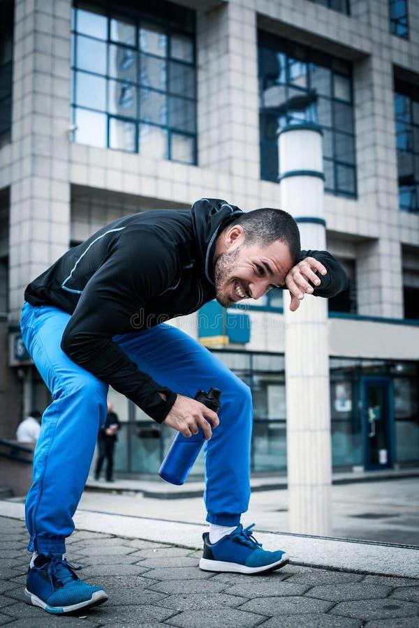 Homem desportivo que toma a ruptura após o exercício foto de stock royalty free