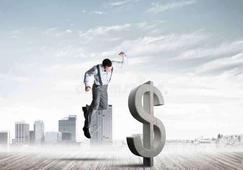 Homem determinado do banqueiro contra a arquitetura da cidade moderna que quebra a figura do concreto do dólar fotos de stock