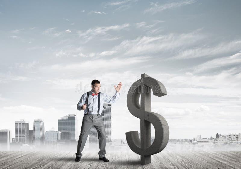 Homem determinado do banqueiro contra a arquitetura da cidade moderna que quebra a figura do concreto do dólar foto de stock