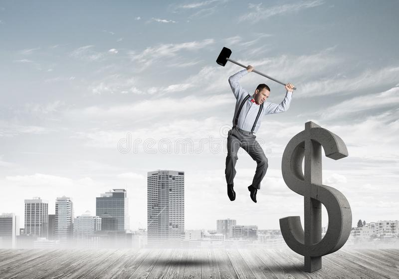 Homem determinado do banqueiro contra a arquitetura da cidade moderna que quebra a figura do concreto do dólar imagem de stock