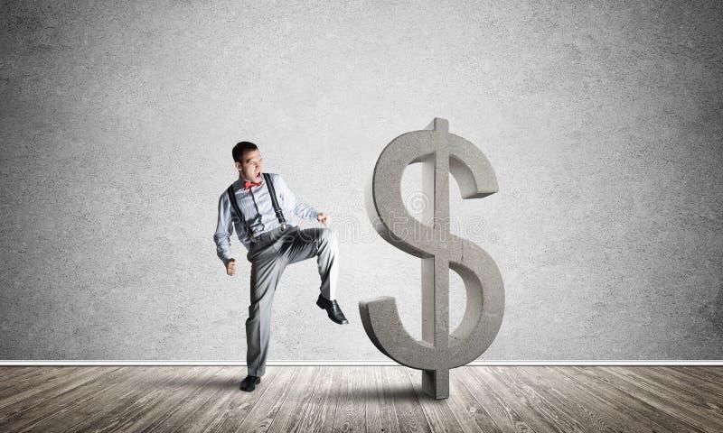 Homem determinado do banqueiro na sala concreta vazia que quebra a figura do dólar fotografia de stock