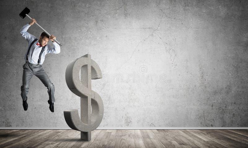 Homem determinado do banqueiro na sala concreta vazia que quebra a figura do dólar imagens de stock